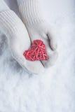 在白色的女性手编织了有纠缠的葡萄酒浪漫红色心脏的手套在雪背景 爱和圣华伦泰概念 免版税图库摄影