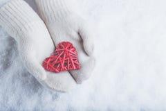 在白色的女性手编织了有纠缠的葡萄酒浪漫红色心脏的手套在雪背景 爱和圣华伦泰概念 库存照片