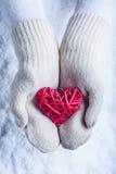 在白色的女性手编织了有纠缠的葡萄酒浪漫红色心脏的手套在雪背景 爱和圣华伦泰概念 免版税库存图片