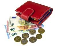 在白色的孤立 欧盟兑现 钞票5, 10, 20欧元 铸造一些 妇女` s红色钱包 库存照片