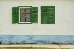 在白色的开放和闭合的绿色窗口上色了葡萄酒别墅 免版税库存照片