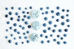 在白色的新近地摘的蓝莓,新鲜的甜蛋白杏仁饼干 平的位置 库存照片