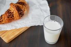 在白色的新鲜的新月形面包弄皱了纸和一个木板有一杯的牛奶 在一张黑暗的木桌上的新近地被烘烤的新月形面包 库存图片