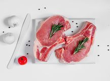 在白色的未加工的ribeye猪肉牛排绘了切板 免版税库存照片