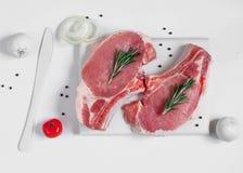 在白色的未加工的ribeye猪肉牛排绘了切板 库存图片
