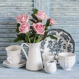 在白色的桃红色玫瑰上釉了投手,在蓝色木土气背景的葡萄酒陶器 在葡萄酒样式的厨房静物画 免版税库存照片
