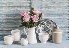 在白色的桃红色玫瑰上釉了投手,在蓝色木土气背景的葡萄酒陶器 在葡萄酒样式的厨房静物画 库存图片