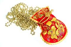 在白色的红色礼物袋子和金装饰链子 免版税库存照片