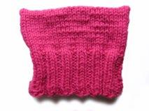 在白色的编织桃红色猫帽子 库存照片