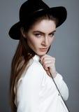 在白色的美好的时装模特儿与黑帽会议 免版税库存照片