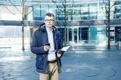 在白色的背景商业查出的人 有书和膝上型计算机的一个人 人通过在街道上的电话讲话 玻璃的人 免版税库存图片