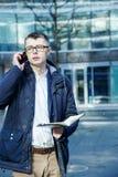 在白色的背景商业查出的人 有书和膝上型计算机的一个人 人通过在街道上的电话讲话 玻璃的人做笔记我 免版税库存图片