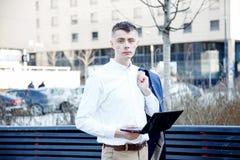 在白色的背景商业查出的人 有书和膝上型计算机的一个人 人通过在街道上的电话讲话 玻璃的人做笔记我 库存照片