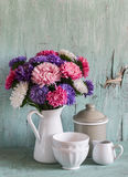 在白色的花翠菊上釉了投手和葡萄酒陶器-陶瓷碗和上釉的瓶子,在蓝色木背景 免版税库存图片