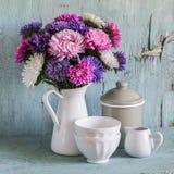 在白色的花翠菊上釉了投手和葡萄酒陶器-陶瓷碗和上釉的瓶子,在蓝色木背景 免版税库存照片