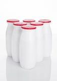 在白色的酸奶容器健康维生素饮料 库存照片