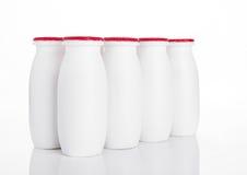 在白色的酸奶容器健康维生素饮料 免版税库存照片