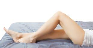 在白色的长的妇女腿 去壳化妆奶油 免版税图库摄影