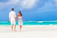在白色的年轻愉快的夫妇在热带海滩 免版税图库摄影