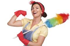 在白色的年轻愉快的美丽的妇女佣人打扫灰尘