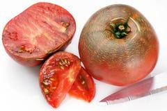 在白色的黑蕃茄 免版税库存图片
