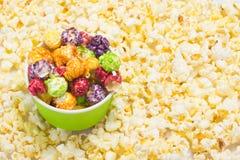 在白色盐味的玉米花背景,一个碗用一个五颜六色,甜纤巧 免版税库存照片