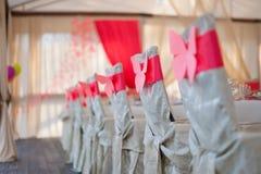 在白色盖子的椅子有一条红色丝带的 免版税库存照片