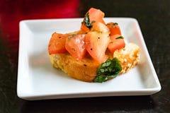 在白色盘子的五颜六色的开胃菜在黑桌上 库存照片