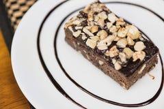 在白色盘的一块果仁巧克力用巧克力汁 免版税库存照片