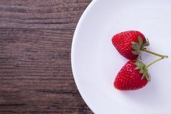 在白色盘的两个红色草莓 免版税库存图片