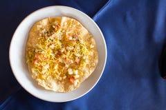 在白色盘的印地安食物Masala papad有蓝色背景 免版税库存图片