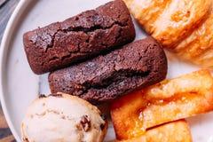 在白色盘的新鲜的被烘烤的物品包括烤饼、新月形面包、金融家和巧克力金融家 免版税图库摄影