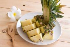 在白色盘的菠萝切片在木头 免版税库存照片