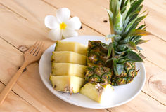 在白色盘的菠萝切片在木头 库存图片