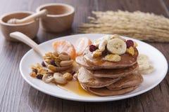 在白色盘的薄煎饼和香蕉顶部早餐 免版税库存图片