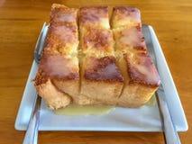 在白色盘的蜂蜜多士和匙子,在木桌上的叉子 免版税库存图片