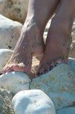 在白色石头的女性腿 免版税库存照片