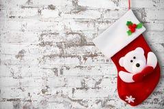 在白色砖墙上的红色圣诞节袜子 免版税库存照片