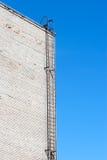 在白色砖墙上的金属梯子 1个背景覆盖多云天空 免版税库存图片