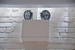 在白色砖墙安装的紧急停电光 免版税库存照片