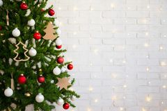 在白色砖墙的圣诞树有光的 库存图片