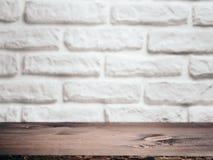 在白色砖墙的空的木桌 产品蒙太奇显示的背景 免版税库存图片