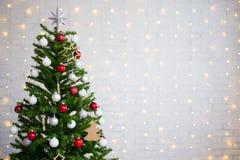 在白色砖墙的装饰的圣诞树有光的 库存图片