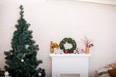 在白色砖墙背景和壁炉的圣诞树 库存照片