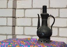 在白色砖墙背景的古老东部黄铜水瓶子 库存图片