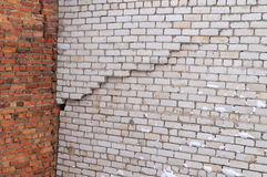 在白色砖瓦房墙壁的垂直的裂缝  免版税库存图片