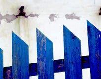 在白色破旧的墙壁背景的蓝色篱芭  免版税库存照片