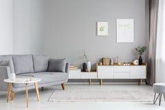 在白色碗柜附近的灰色长椅最小的客厅内部的 库存照片
