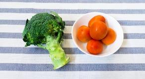 在白色碗的五个蕃茄用在镶边背景的硬花甘蓝 图库摄影