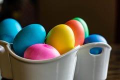 在白色碗的五颜六色的复活节彩蛋安排 免版税库存图片
